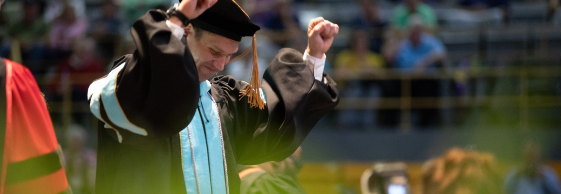 Doctoral Student graduating, walking across stage with arms raised
