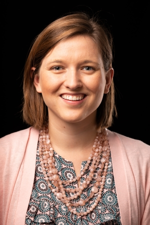 Headshot of Ashley Pennell - woman wearing pink sweater, patterned shirt and pink necklace